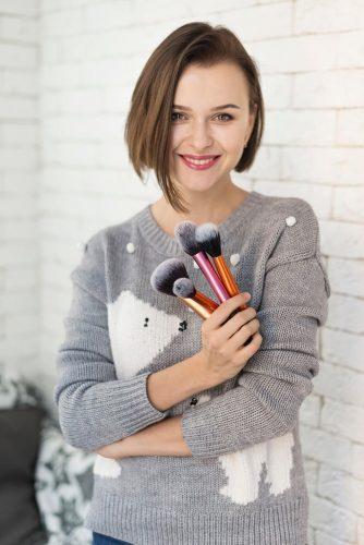 Smiling girl holding makeup brushes