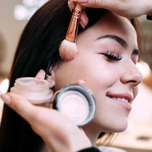 Girl is smiling doing makeup